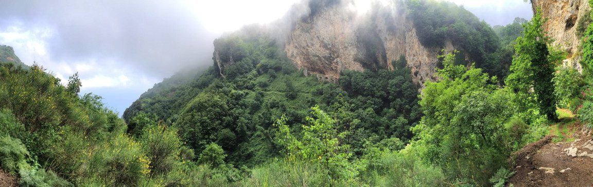 Hiking on the Amalfi Coast, stage 3, green valley with rocks and fog below San Lazzaro